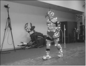 gait study participant equipped with surface electrodes, footswitches, and passive reflective markers walking on force plate sensors