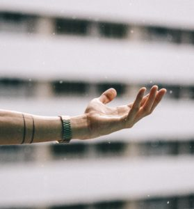 photograph of an arm reaching into the sky to feel the rain in the palm of their hand