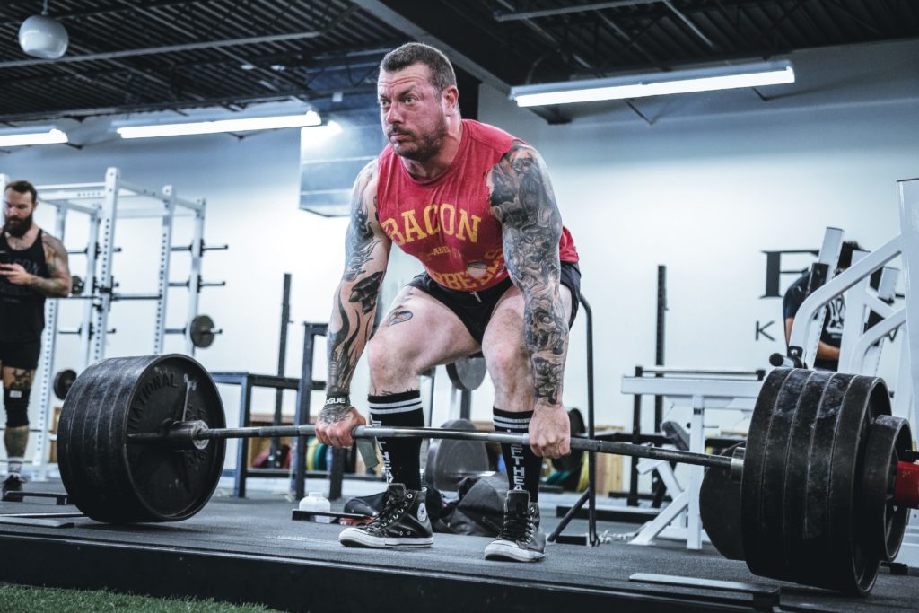 A large tattooed man deadlifting enough weight to bend the bar in the conventional form.