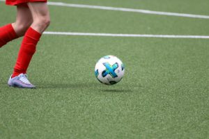Woman plays soccer on artificial turf field