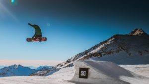Snowboarder grabbing board while in the air after going off a jump.