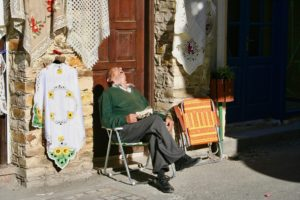Elderly man sitting in the sun, asleep with head back and mouth open.