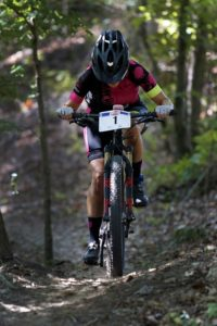 A woman fights up a steep hill in a mountain biking race
