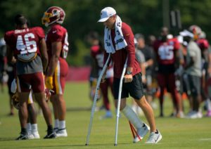 An athlete walking on crutches across the field - from The Washington Post