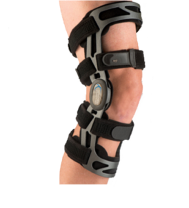 A PCL brace is shown in place on a knee. There are two stabilizing straps above the knee, and two below the knee. They are connected by a metal frame that meets at a hinge joint over the side of the knee.