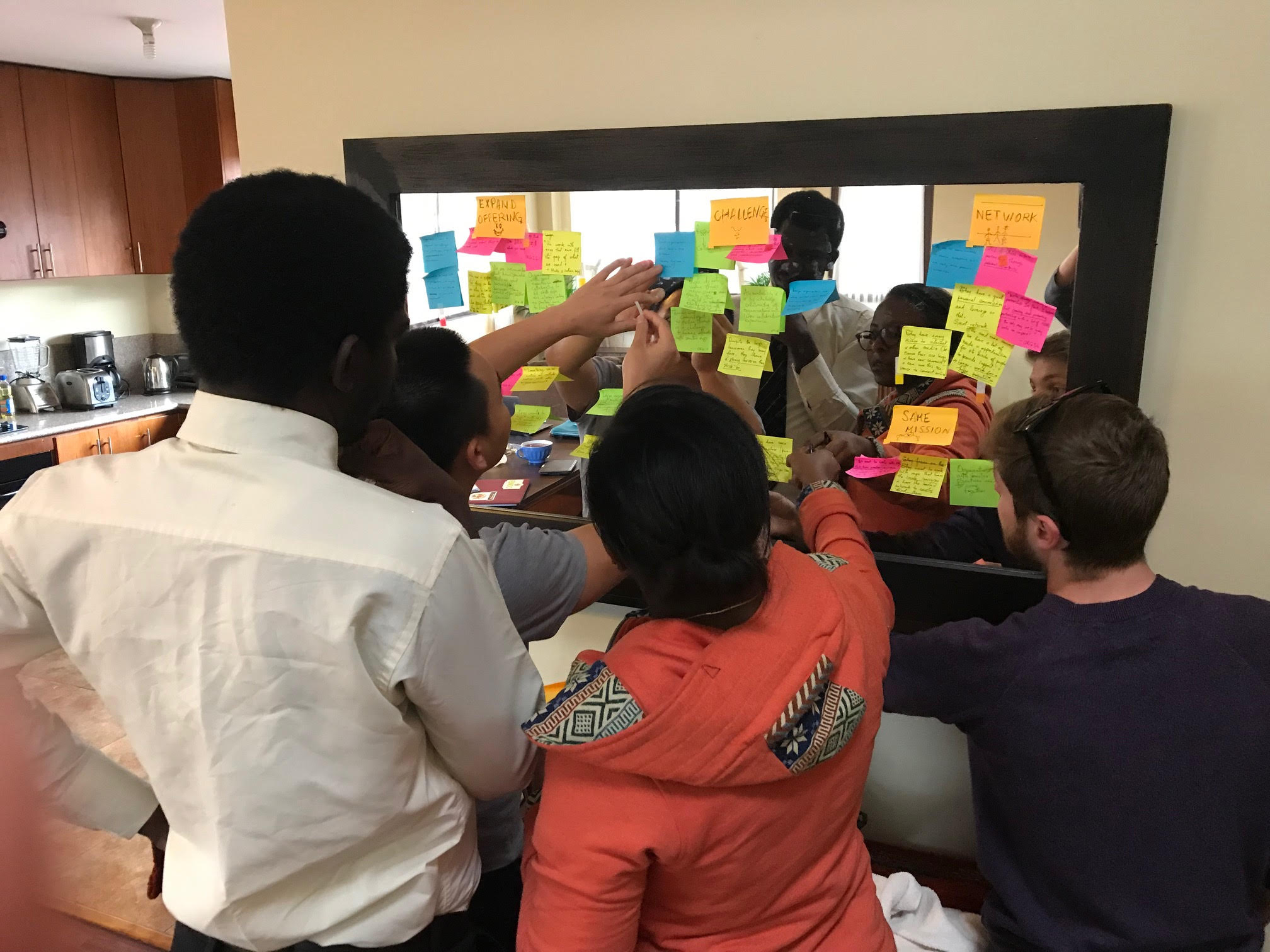 MGA i-Lab students plan their projects on a mirror with bright-colored sticky notes.