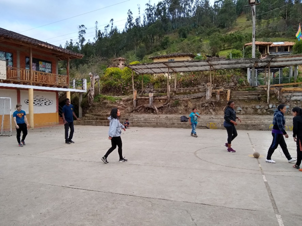 MGA student Max Ngoc Nguyen playing soccor with community members in a plaza in Ecuador.