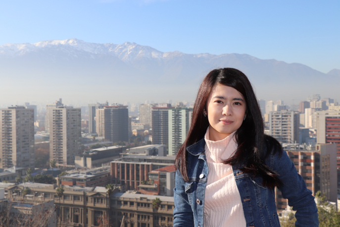 MGA student Mukhlisa Khudayberganova stands on a hill overlooking the city of Santiago. The Andes mountains can be seen in the background.