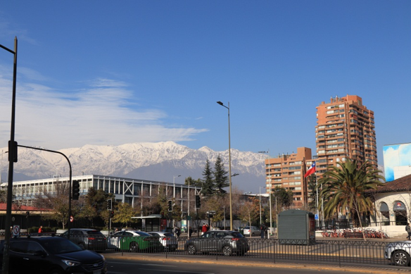 A city street in Santiago. The Andes are seen in the background, and the sky is blue.