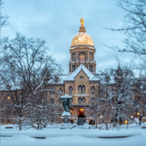 A landscape with trees, ground and a statue of the Sacred Heart of Jesus covered in snow. The Golden Dome of the Main Building has snow on its roof in the background with a gray sky at twilight.