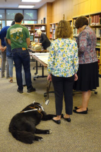 Photo of service dog and student in class in special collections