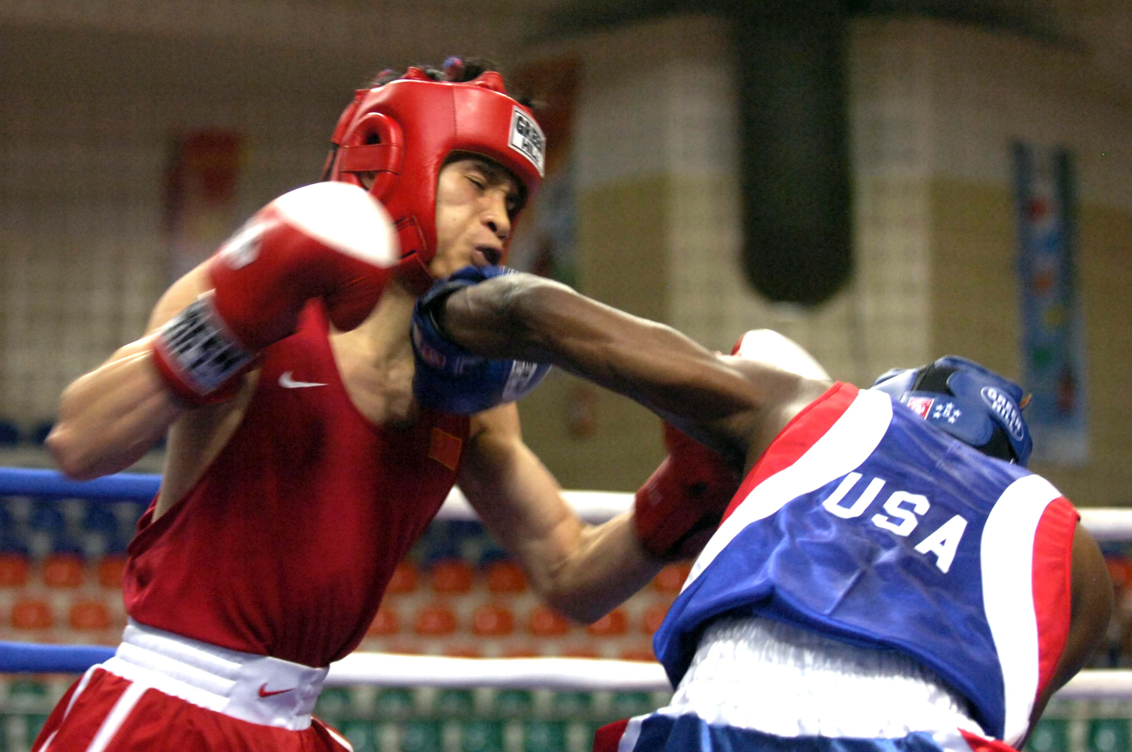 Image of two boxers competing in the ring with headgear