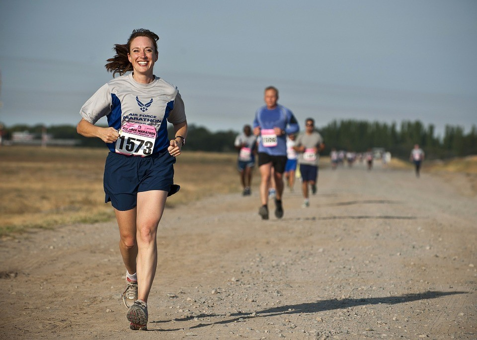 A woman running a race bursts ahead of her male competitors while smiling.