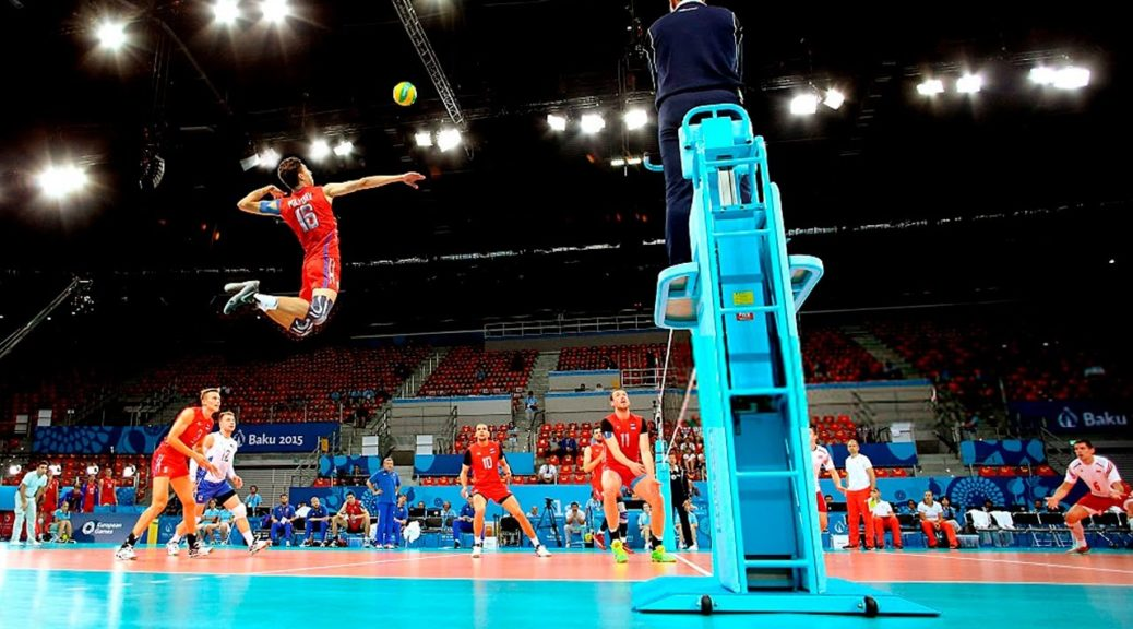 A high flying volleyball player getting ready to hit the ball