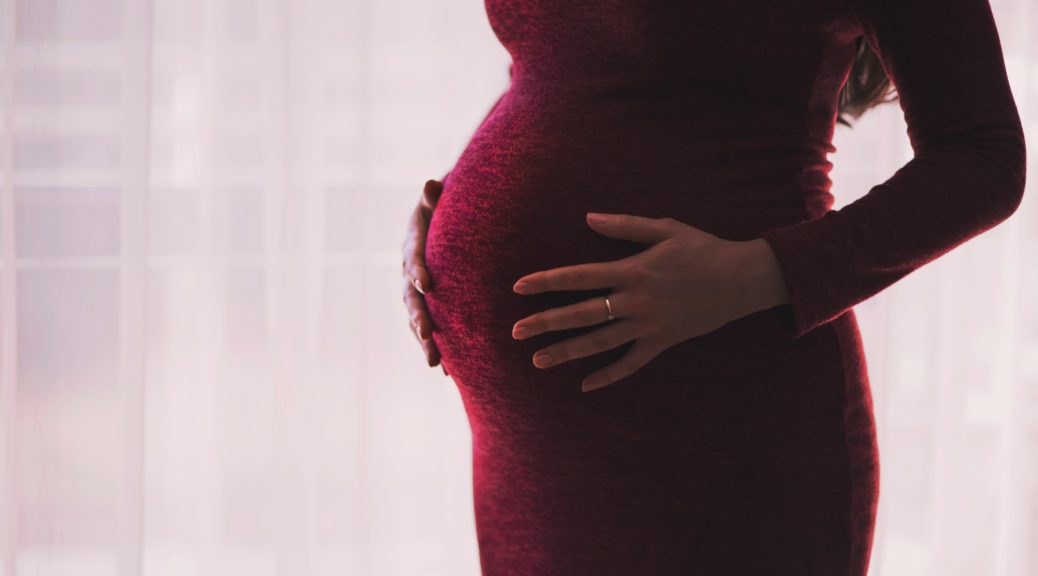 Pregnant woman torso holding belly