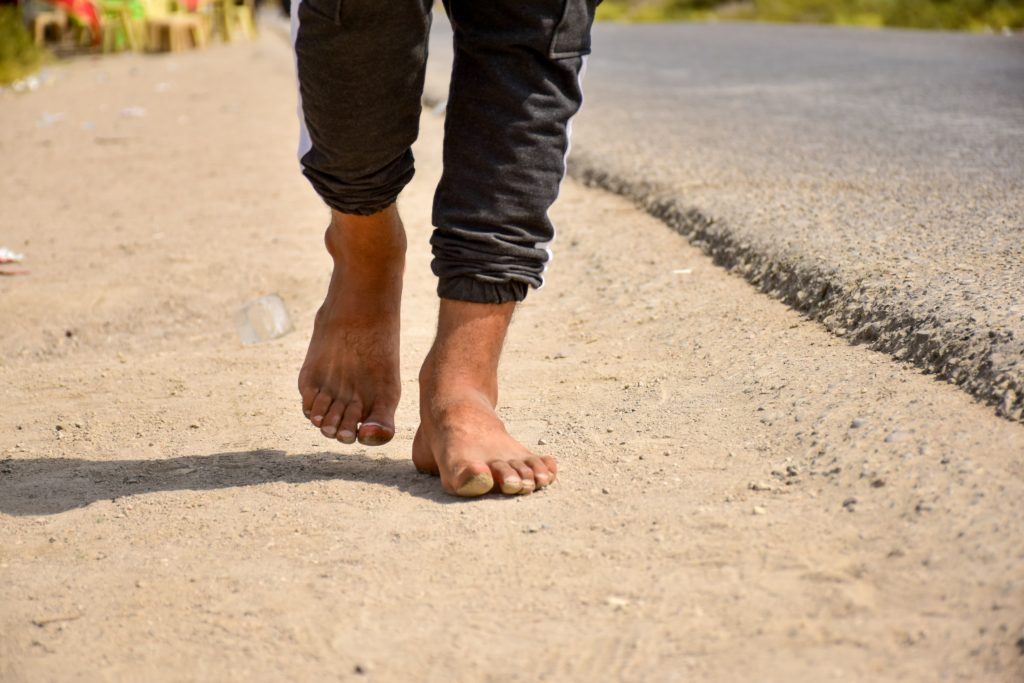 barefoot person walking outdoors during the day