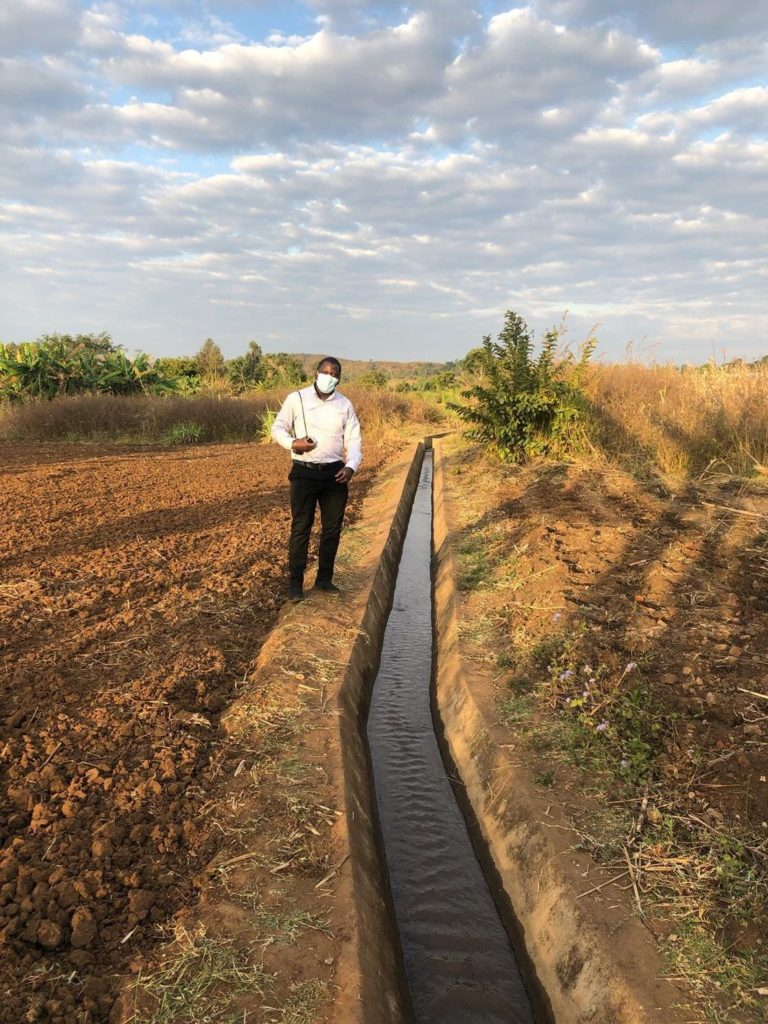 My classmate Arthur Ssembajja, standing next to an irrigation canal in Natama, Chiradzulu, southern Malawi during our tour of the community's watershed treatment structures.