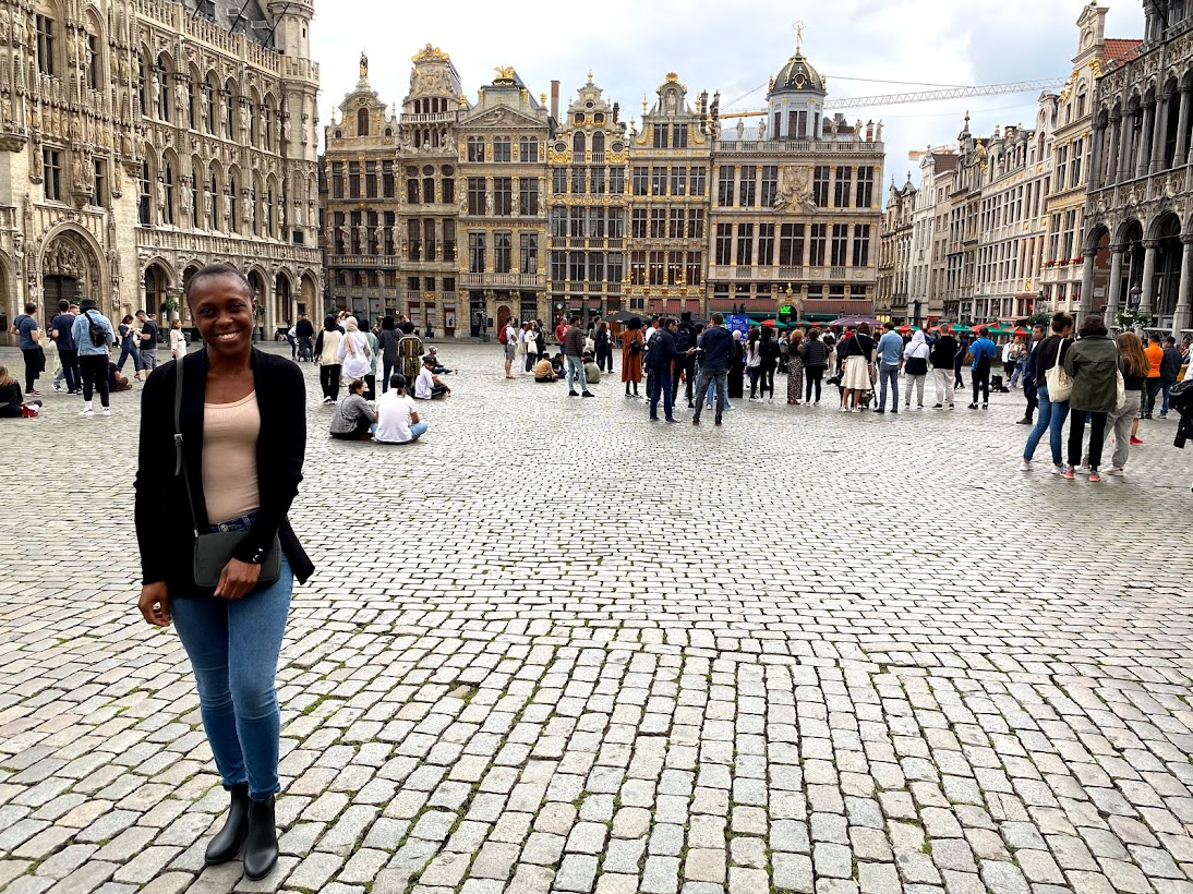 Sarah Nanjala at the Grand-Place in Brussels surrounded by Gothic buildings