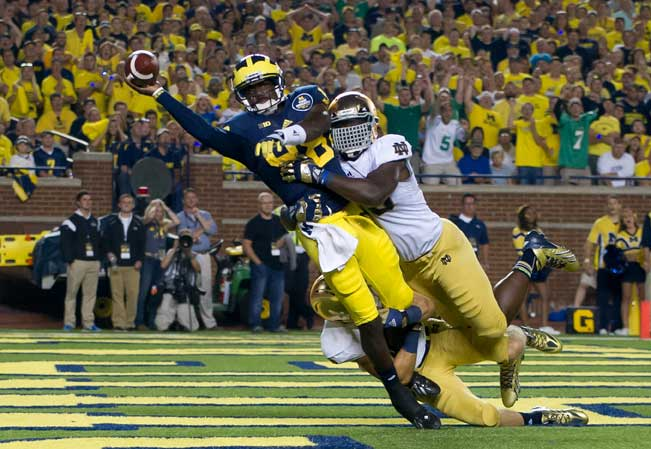 Sept. 7, 2013; Michigan Wolverines quarterback Devin Gardner (98) throws while being tackled by Notre Dame Fighting Irish linebacker Prince Shembo (55) and safety Austin Collinsworth (28) in the fourth quarter. Photo by Matt Cashore
