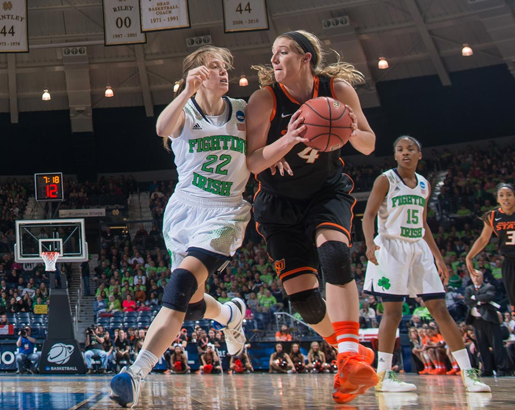 Mar 29, 2014; Oklahoma State Cowgirls forward Liz Donohoe (4) dribbles as Notre Dame Fighting Irish guard Madison Cable (22) defends in the regional semifinal game against Oklahoma State. Notre Dame won 89-72.
