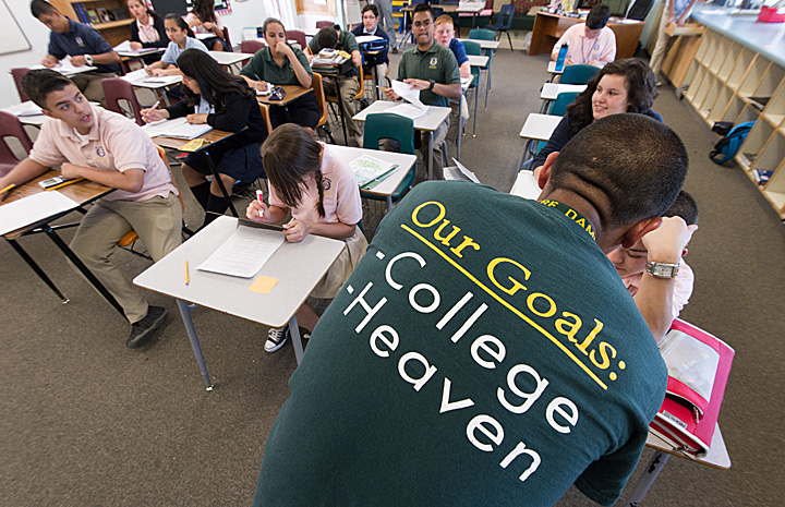 ACE teacher Matthew Gring wears a t-shirt proudly displaying the ACE Academy goals: College and Heaven, as he teaches his class at St. Ambrose School in Tucson, AZ.