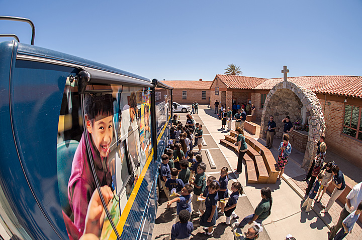 Students at St. Ambrose School in Tucson, Arizona gather around the ACE bus to find their school's name.