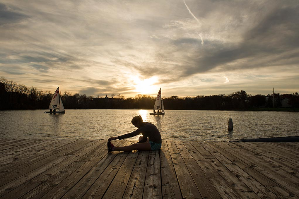 Nov. 5, 2014; Enjoying the unseasonably warm temperatures, sophomore psychology and pre-med student, Patty Morrow stretches after her afternoon jog around St. Joseph Lake. (Photo by Barbara Johnston/University of Notre Dame)