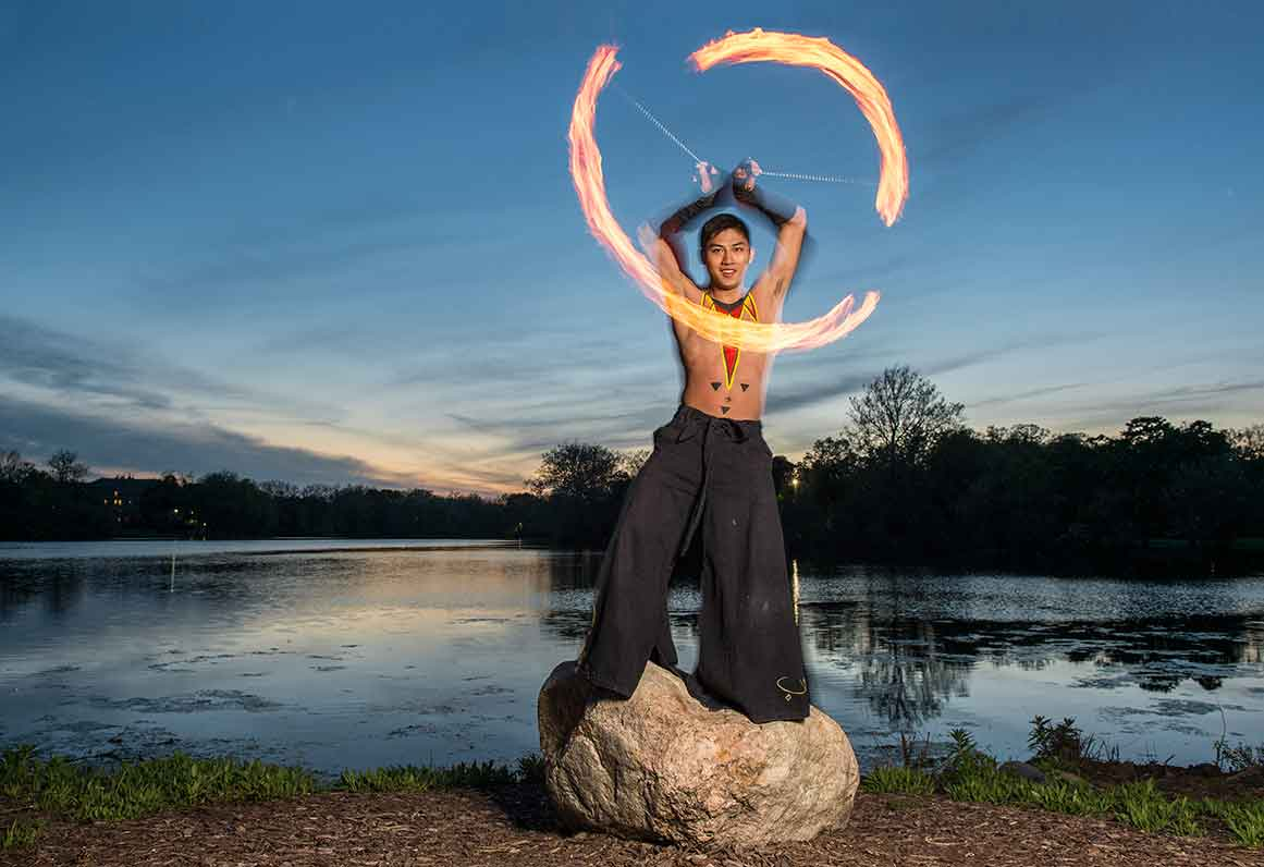 May 13, 2015; Senior Mark O'Dea demonstrates his fire dancing skills on the shore of St. Mary's Lake. (Photo by Barbara Johnston/University of Notre Dame)