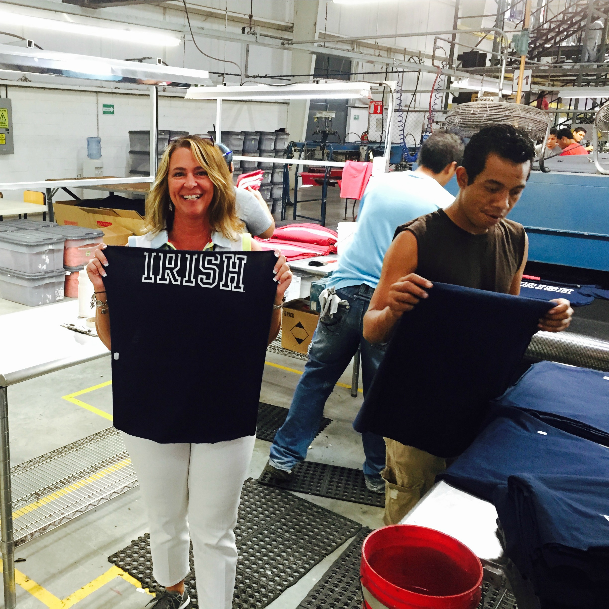 Tomi Gerhold with League factory workers as officially licensed Notre Dame shirts are made.