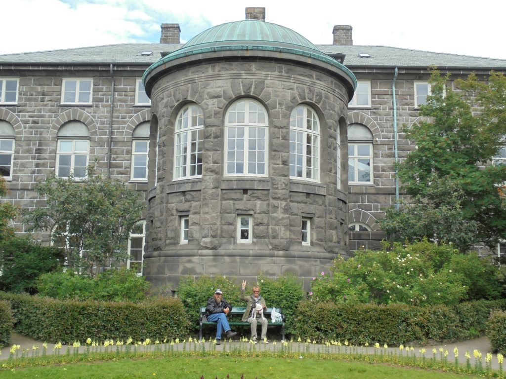 Two Icelanders sit in the garden behind the parliament building (Alþingi).
