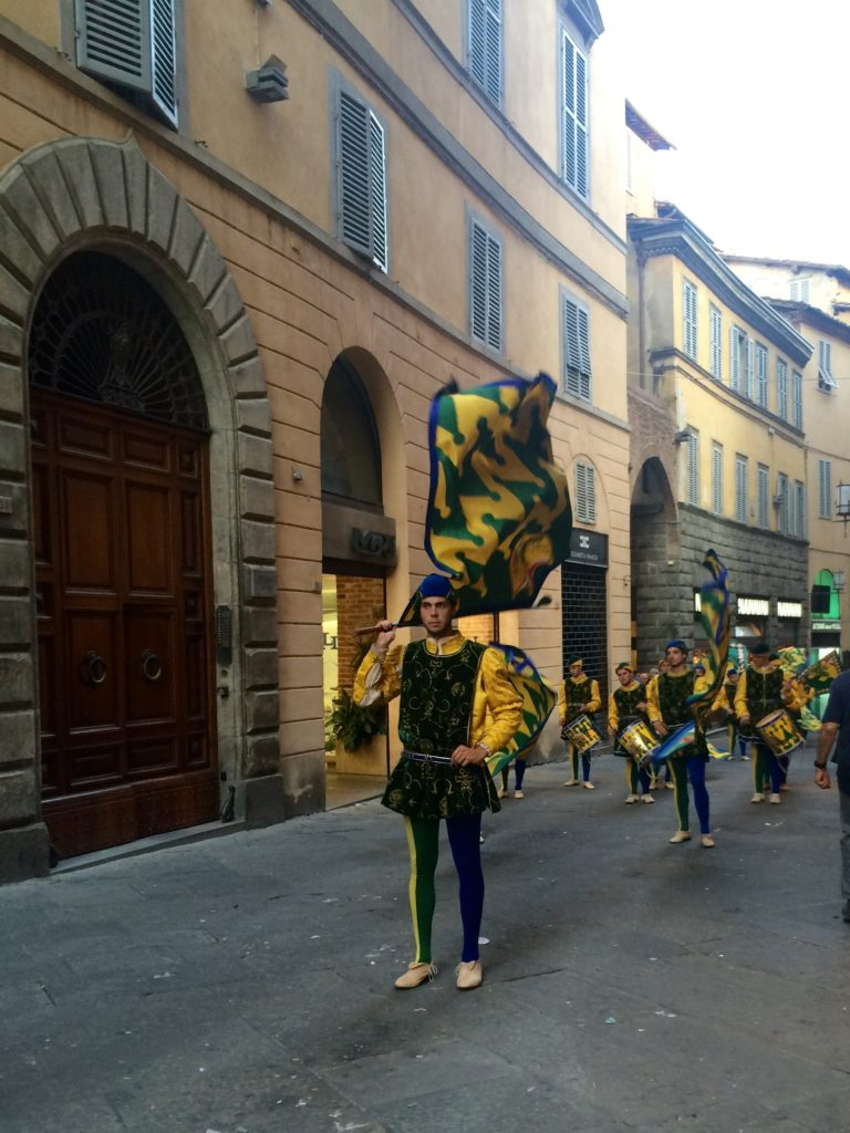 The people from the Bruco contrada (caterpillar!) marching with their flags, drums and medieval costume